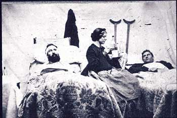 A Civil War nurse attending to two injured soldiers
