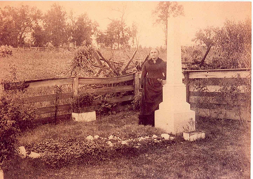 Jesse James' mother, Zerelda, standing next to his grave on the family farm