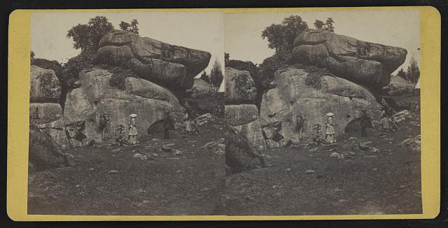 Stereograph showing a woman walking past the Devil\'s Den rock formations in Gettysburg, Pennsylvania circa 1863-1880