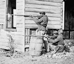 Two African-American soldiers at an abandoned farmhouse in Dutch Gap, Virginia in 1864