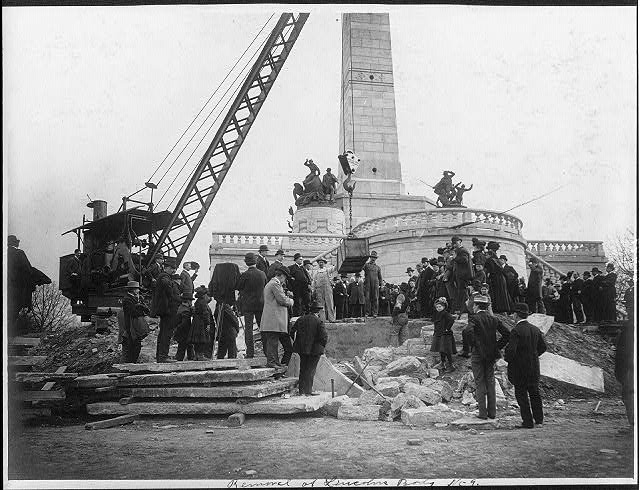 Large crowd watching crane lift box containing Abraham Lincoln's body in front of Lincoln tomb at Springfield, Illinois, circa April of 1901